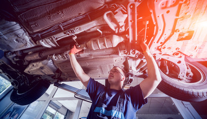 Car mechanic repair car suspension of lifted automobile at repair service station