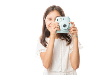 Portrait on a young girl clicking photos with camera isolated on white background