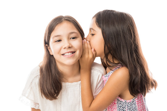 Younger sister whispering gossip to her elder sister on white background