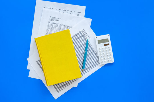 Math textbook or tutorial near sheet with numbers, countes and calculator on blue background top view copy space