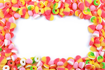 Frame of assorted gummy candies isolated on white. Top view. Space for text or design.