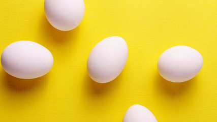 Organic white eggs on yellow pastel backgound.