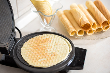 Waffle iron in the kitchen. Preparing homemade waffles, pouring a dough
