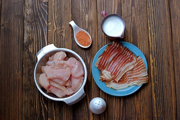 Ignidients for chicken fillet wrapped with smoked bacon, on a wooden background. Raw chicken fillet, buttermilk, spices, smoked bacon, salt.