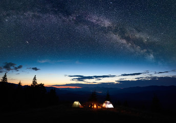 Family tourists mother, father, two sons resting at night camping in mountains, sitting on log beside campfire and two illuminated tents, enjoying amazing view of evening sky full of stars, Milky way