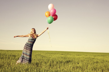 Girl with balloons in the field. Solar and positive energy of nature. Young beautiful woman on the grass in the Park.