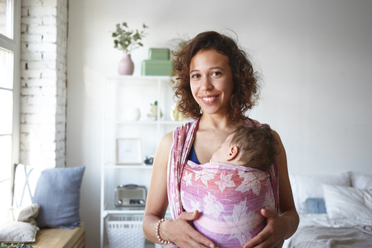 Portrait of joyful young dark skinned female enjoying new babywear for carrying toddler, making life easier. Happy housewife smiling after she finished cleaning, with her child sleeping in baby sling