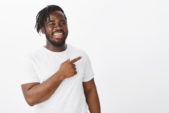 Joyful friendly african-american bearded man in white t-shirt, pointing at upper left corner, smiling and laughing from happiness and positive emotions, being glad sharing amazing copy space