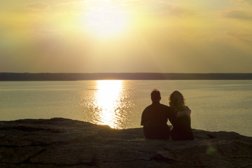 young couple in love sits hugging on the lake shore overlooking the sunset. Happy people.