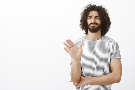 No thanks, I pass. Displeased uninterested handsome curly-haired male in stylish striped t-shirt, waving palm in no or stop gesture, crossing chest with hand, smirking with dislike while rejecting