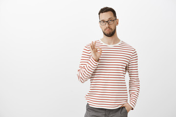Not bad, like your idea, good job. Satisfied impressed attractive mature guy in glasses and striped clothes, showing ok or okay sign and making pleased expression, giving permission over gray wall