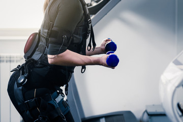 Closeup photo of woman in EMS suit exercising with dumbbells