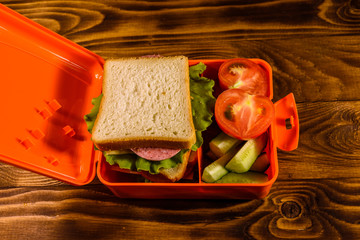 Lunch box with sandwich, cucumbers and tomatoes on wooden table