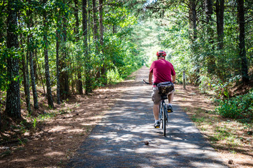 Adult senior man riding a bicycle on a trail through the forest. Fun recreational outdoor activity and exercise of biking. Enjoying the outdoors during relaxing vacation.