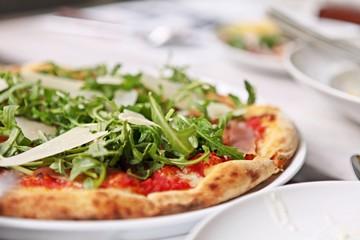 Delicious and freshly baked Prosciutto di Parma pizza or pizza with Tomato, mozzarella, prosciutto, Arugula and Parmesan cheese. Natural light.