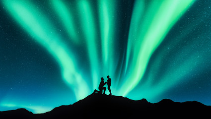 Northern lights and silhouettes of a man making marriage proposal to his girlfriend on the hill. Landscape with night starry sky, aurora borealis, couple. People. Lovers and polar lights. Travel