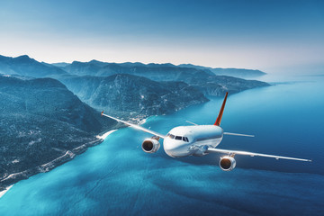 Poster Avion à Moteur Aircraft is flying over islands and sea at sunrise in summer. Landscape with white passenger airplane, seashore, mountains, forest, clear sky, and blue water in bright day. Travel and resort. Tourism