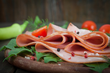 Sliced ​​mortadella on wooden chopping board with vegetables on the background
