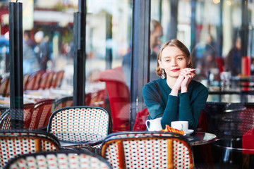 Young elegant woman drinking coffee in cafe in Paris, France