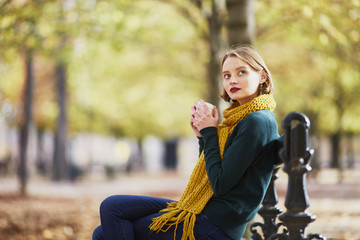 Happy young girl in yellow scarf walking in autumn park