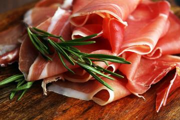 Italian prosciutto crudo or jamon with rosemary. Raw ham.