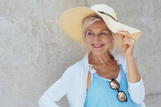 Smiling mature blonde woman wearing summer hat