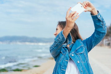 Woman taking a selfie looking back at the sea