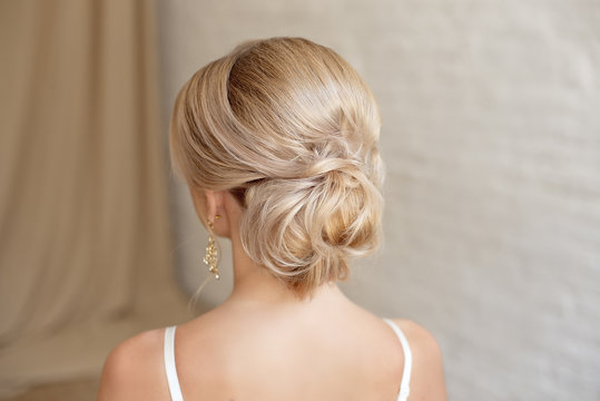 Rear view of female hairstyle middle bun with blond hair.