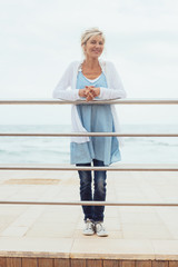 Trendy blond woman standing on a wooden pier