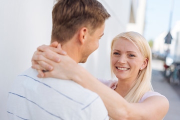 Smiling happy woman hugging her husband