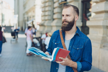 Bearded man sightseeing with a map and guide book