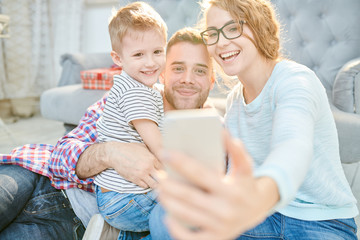 Warm toned portrait of loving young family with cute little son playfully taking selfie at home  in sunlight