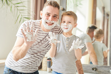 Warm toned waist up  portrait of handsome dad teaching cute little son how to shave, posing mirror with faces covered in foam in modern bathroom