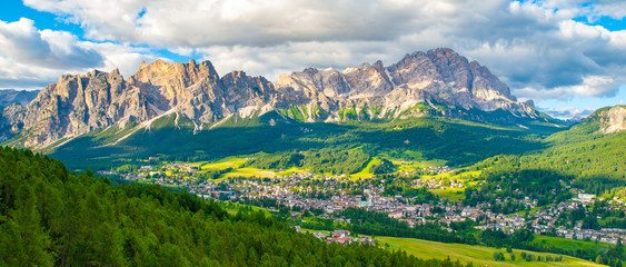 Panorama of Cortina d'Ampezzo with green meadows and alpine peaks on the background. Dolomites, Italy Wall mural