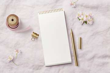 romantic feminine mockup with open / blank notebook, pink ribbon, writing supplies and cherry flowers on a soft linen background, top view