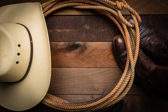 A cowboy hat, lariat rope and boots on a wooden plank background