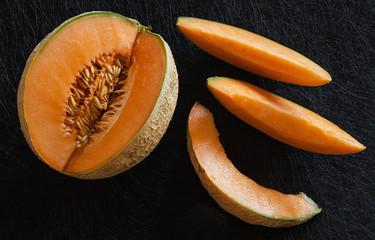 Sliced ripe melon on black background