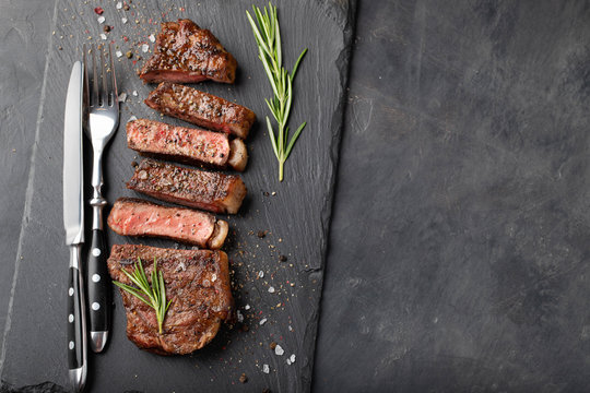 Closeup ready to eat steak new York beef breeds of black Angus with herbs, garlic and butter on a stone Board. The finished dish for dinner on a dark stone background. Top view with copy space