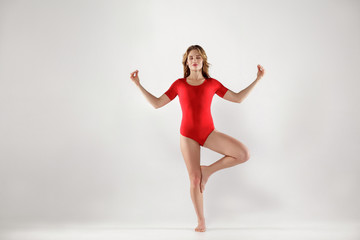 attractive woman in red leotard standing on one leg and doing tree yoga pose