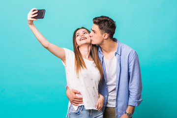 Beautiful couple having a fun together making selfie on blue background.