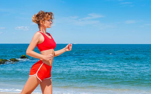 Beautiful young woman in sportswear running on beach.