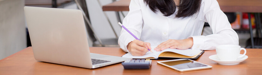 Closeup banner asian woman writing on notebook on table with laptop, girl work at coffee shop, freelance business concept. Wall mural
