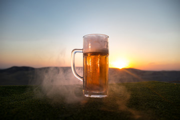 Close Up of A Glass of Draught Beer with the Bokeh of Sunlight Background, beer on grass.
