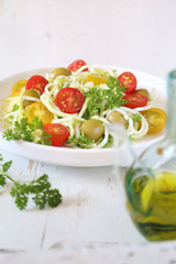 Vegetarian food: raw zucchini spaghetti salad with cherry tomatoes, olives and olive oil