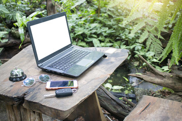 Computer laptop with blank white screen on wooden table with green garden