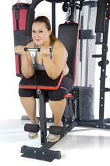 Beautiful fat woman exercises with weight machine