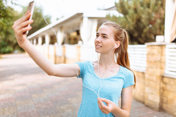 Girl after a morning jog takes a selfie on the phone, training
