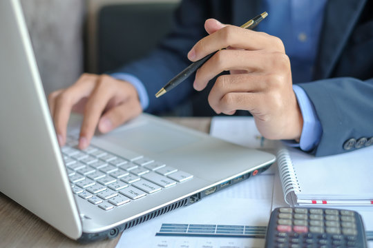 Businessman using laptop for analysis maketing plan, Manager calculate financial report and graph chart.  Business, Finance and Accounting concepts