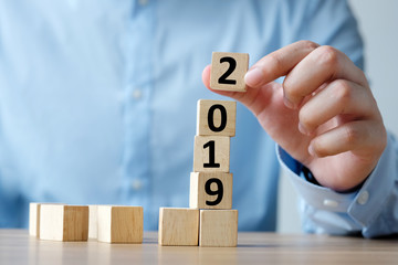 2019 new year greeting card, Hand holding wooden cubes with 2019