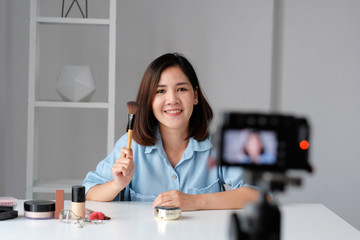 Young asian woman beauty blogger showing how to make up video tutorial, vlog concept, people and technology communication